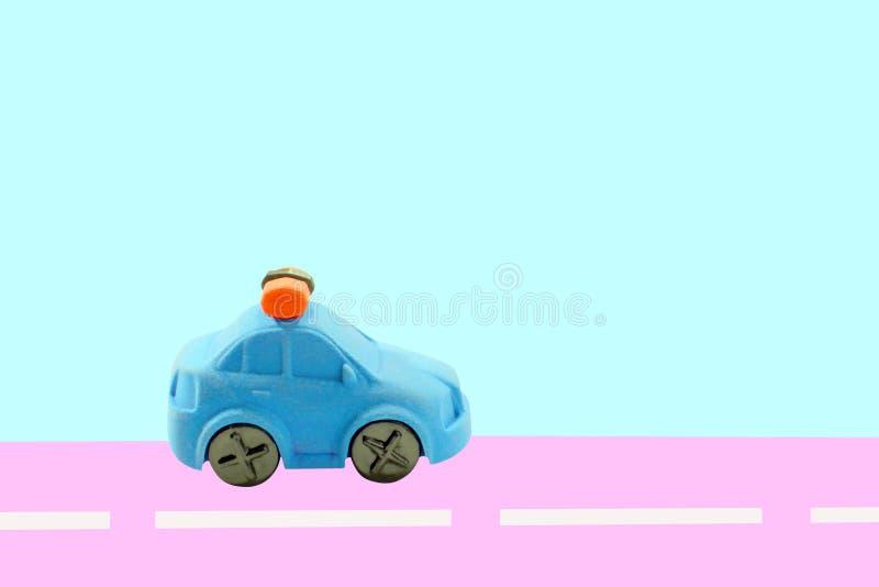 Błękitny samochód na błękitnym odosobnionym tle, rusza się wzdłuż różowej trasy zdjęcie stock