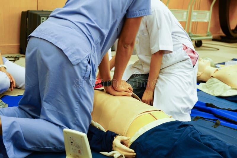 Błękitny smokingowy praktykant pielęgniarki spełniania klatki piersiowej ściskanie na mężczyzna zdjęcie stock