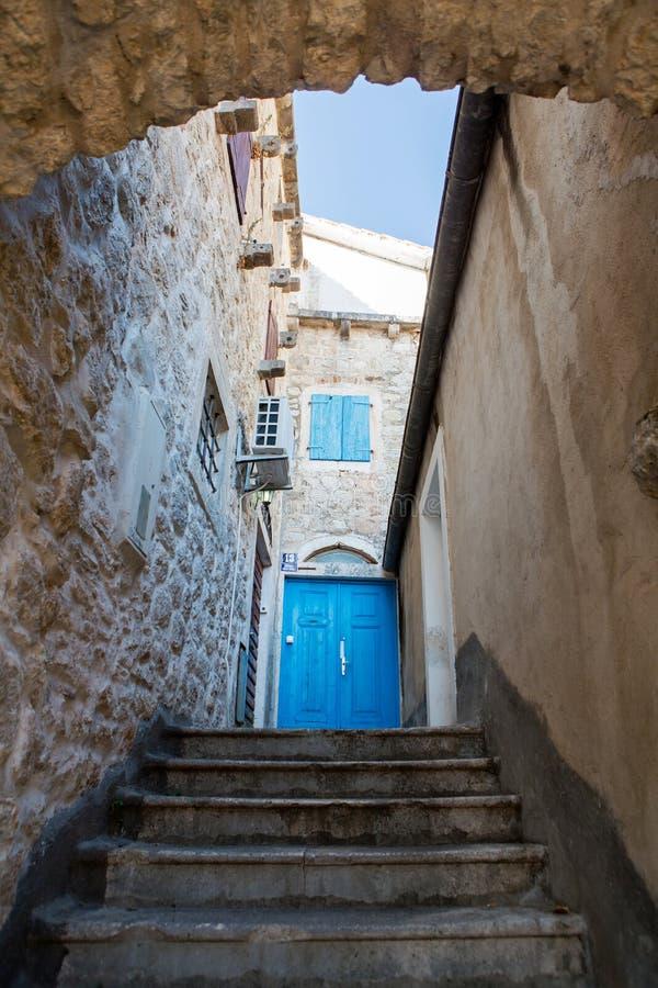 Błękitny stary drewniany drzwi w kamiennym domu z schodkami zdjęcia royalty free