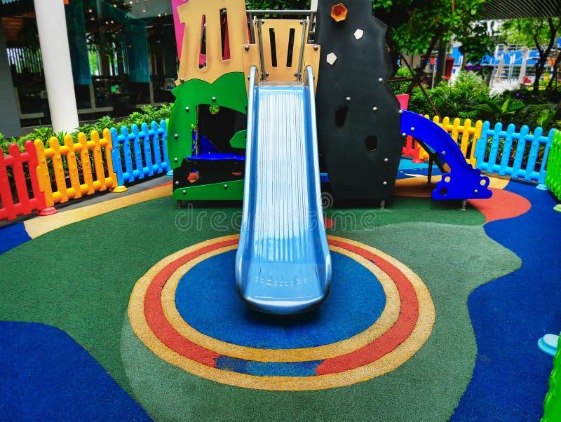 Błękitny suwak dla dzieciaków przy Kolorowym boiskiem obraz royalty free