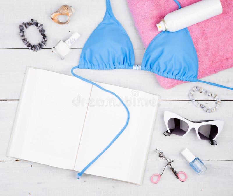 błękitny swimsuit, książka, różowy ręcznik, kosmetyka makeup, bijou i podstawy na białym drewnianym biurku, zdjęcia royalty free