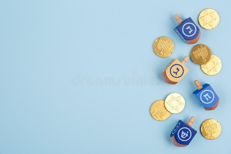 Błękitny tło z multicolor czekolad monetami i dreidels Brzęczenia fotografia stock