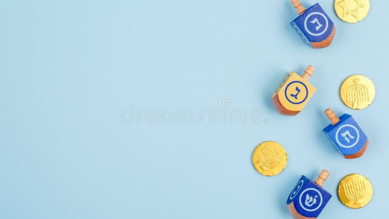 Błękitny tło z multicolor czekolad monetami i dreidels Brzęczenia obrazy stock