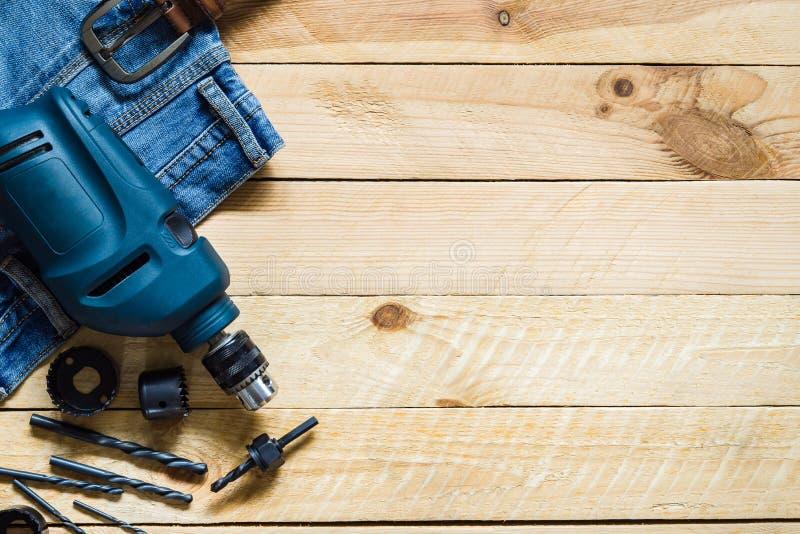 Błękitny zasilanie elektryczne świder z setem kawałek i niebiescy dżinsy na grug zdjęcie royalty free