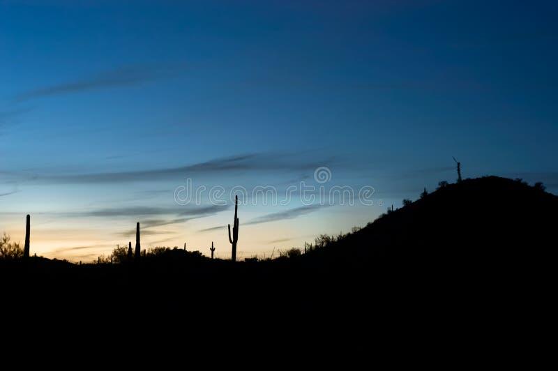 Błękitny zmierzch zaraz po zmierzchem jarzy się za pustynnymi wzgórzami fotografia stock