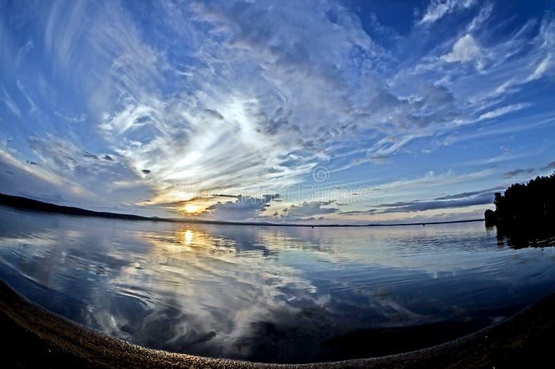 Błękitny zmierzchu niebo z malowniczymi chmurami odbija w spokojnym jeziorze fotografia royalty free