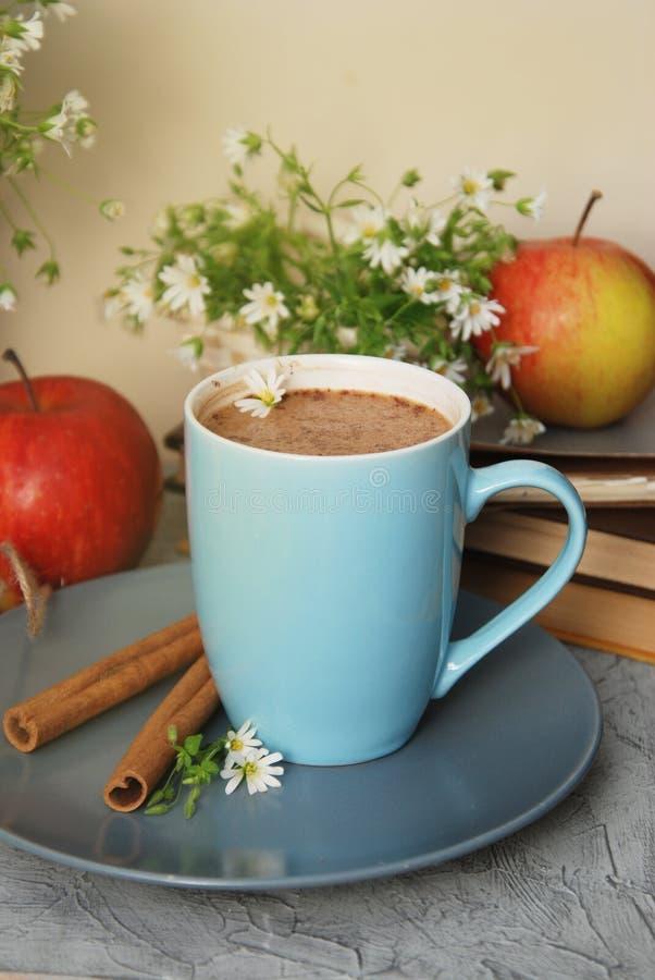 Błękitnych filiżanki kawy mleka napoju cynamonowych kijów gorących książek jabłek rumianku Czerwony kwiat Buquet fotografia stock