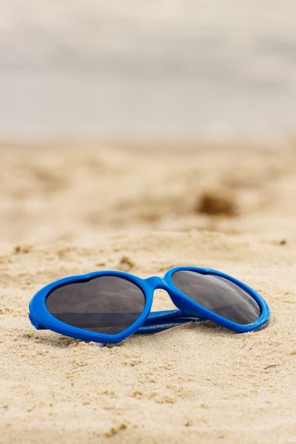 Download Błękitnych Okularów Przeciwsłonecznych Kształtny Serce Na Piasku Zdjęcie Stock - Obraz złożonej z nadmorski, foremność: 57654540