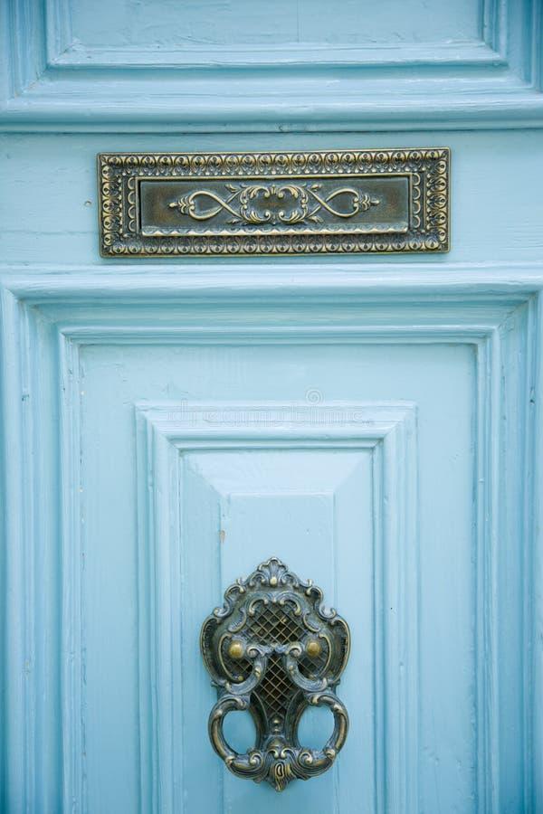 Bławy drewniany wejściowy drzwi z ornated knocker i znakiem obrazy stock