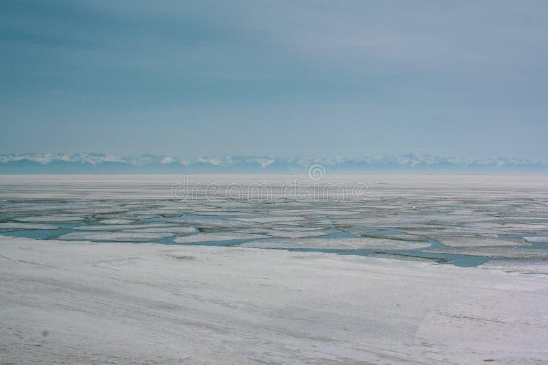 Bławy krajobraz z widokiem jeziora zakrywającego z falcowanie lodem G?ry na horyzoncie obraz stock