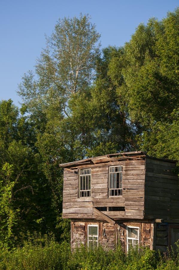Bławy niebo w ciepłym lecie nad starym zaniechanym domem budował od drewnianego w lasowej zieleni drzewach daleko blisko Travelli obraz stock
