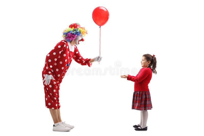Błazen daje balonowi dziewczyna troszkę zdjęcia stock