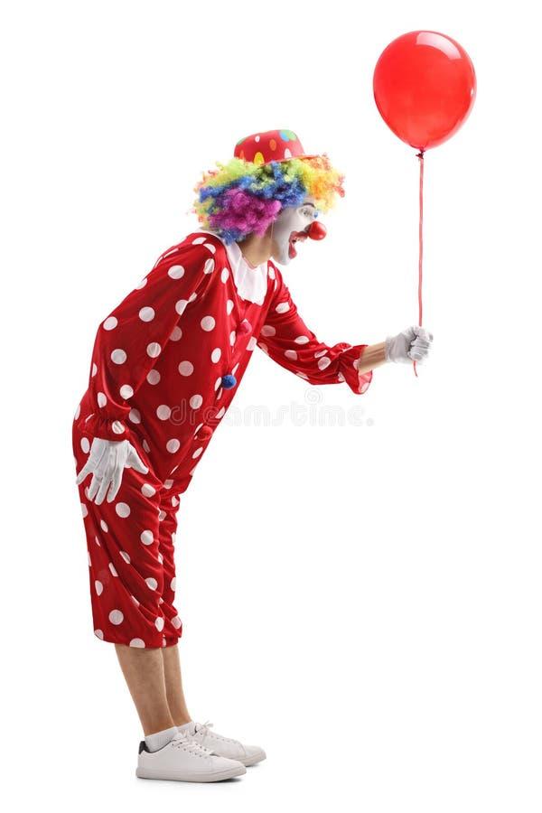 Błazen trzyma czerwonego balon zdjęcia stock