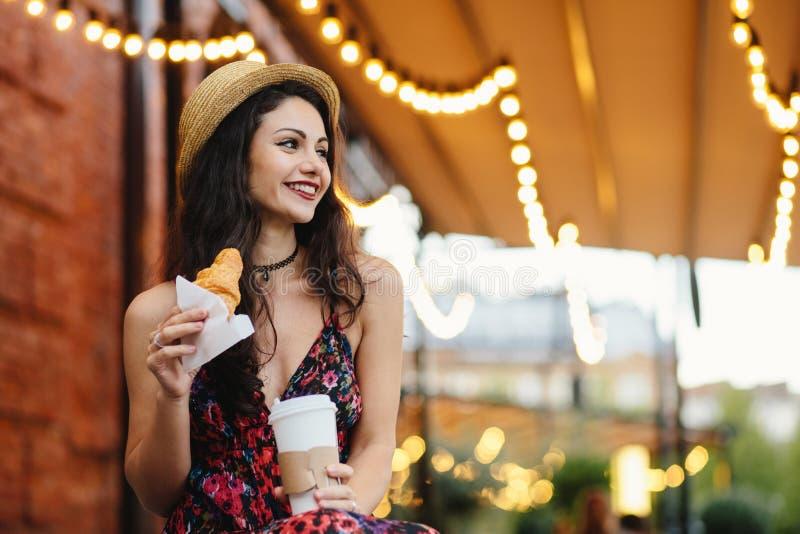 Błoga brunetki kobieta jest ubranym lato kapelusz, sukni mienia croissant i takeaway kawa odpoczywa przy z przyjemnym pojawieniem zdjęcie royalty free