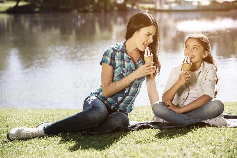 Błogi obrazek matka i córka siedzi wpólnie blisko jeziora i je lody Młoda kobieta jest przyglądająca i zdjęcia stock