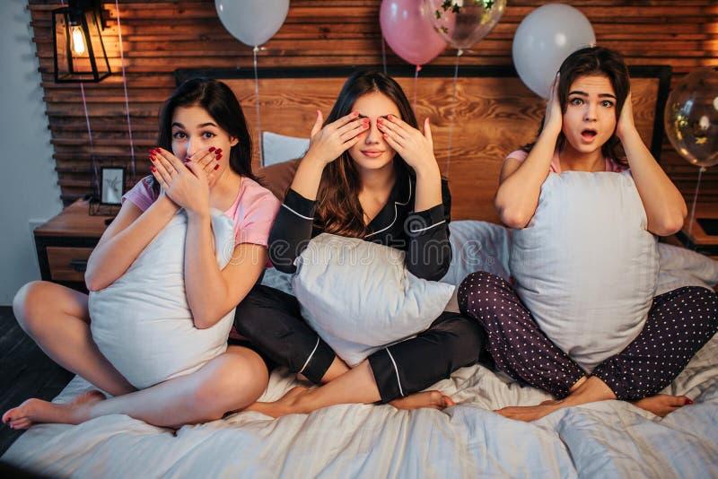 Błogie i śmieszne młode kobiety siedzą na łóżku w świątecznym pokoju Utrzymują nogi krzyżują Pierwszy modela okładkowy usta, seco zdjęcie royalty free
