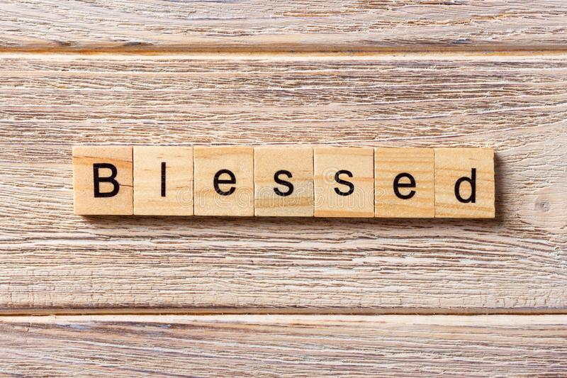 Błogosławiony słowo pisać na drewnianym bloku Błogosławiony tekst na stole, pojęcie zdjęcie royalty free