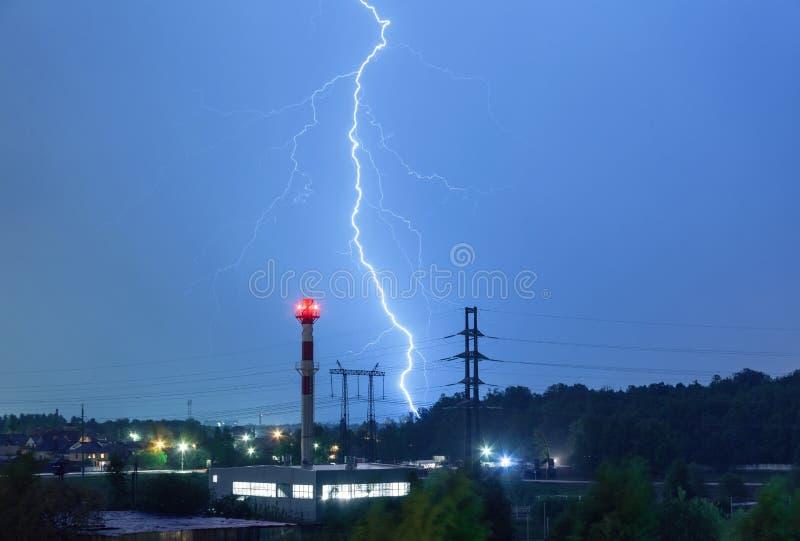 Błyskawica w nocnym niebie nad kotłowym domem liniami energetycznymi i fotografia royalty free