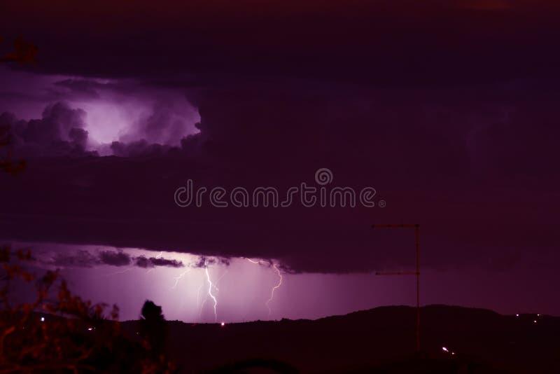 Błyskawica w odległości między grzmot burzy chmurami zdjęcie stock