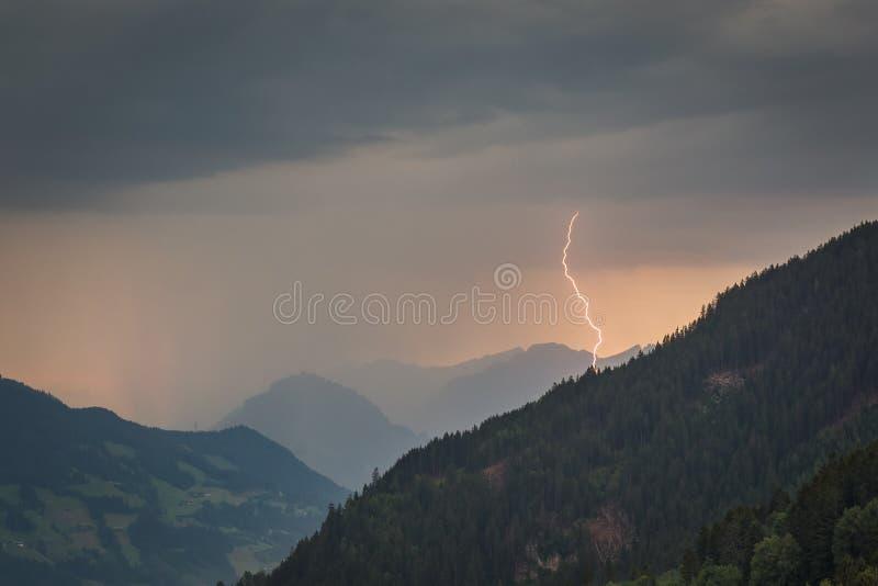 Błyskawicowy rygiel uderza w dolinie od wysokogórskiej wieczór burzy zdjęcia stock