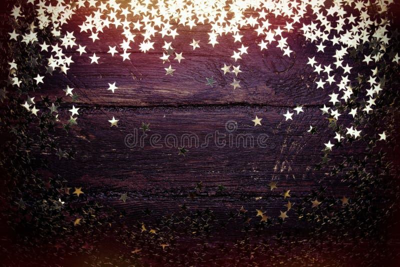 Błyskotliwość złote gwiazdy na grunge drewna tle obraz royalty free