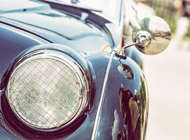 Błyszczący błękitny rocznika samochód, szczegółu reflektor widok, fotografii filt fotografia stock