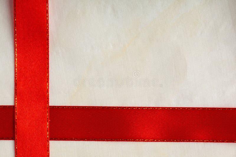 Błyszczący czerwony tasiemkowy lampas na jaskrawym sukiennym tle zdjęcia stock