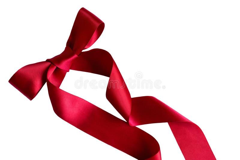 Błyszczący dekoracyjny czerwony atłasowy faborek z łękiem na białym tle, zdjęcie royalty free