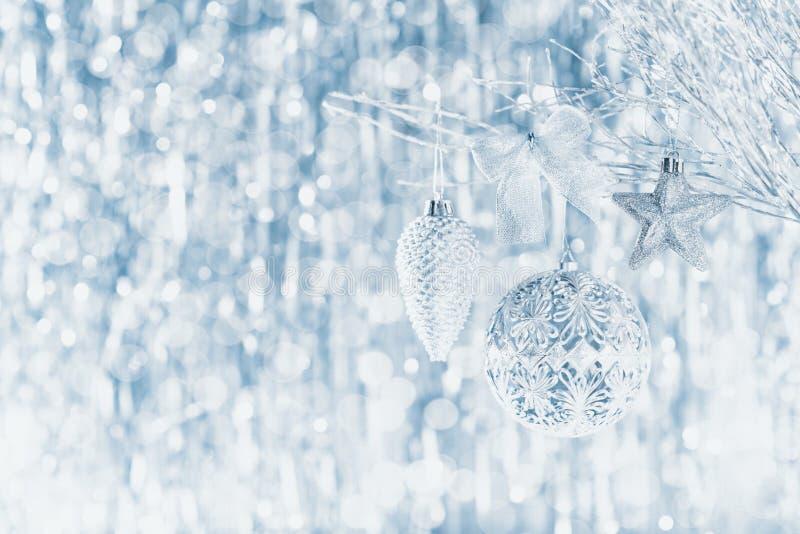 Błyszczący srebni boże narodzenia ornamentują obwieszenie na drzewie z defocused bożonarodzeniowymi światłami, zdjęcie stock
