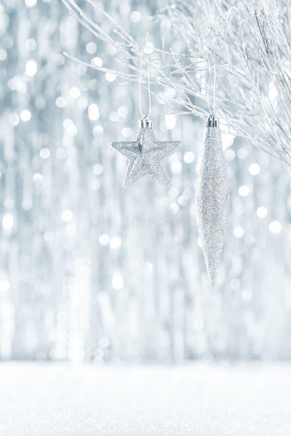 Błyszczący srebni boże narodzenia ornamentują obwieszenie na drzewie z defocused bożonarodzeniowymi światłami, zdjęcia royalty free