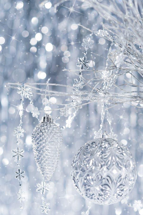 Błyszczący srebni boże narodzenia ornamentują obwieszenie na drzewie z defocused bożonarodzeniowymi światłami, obraz stock