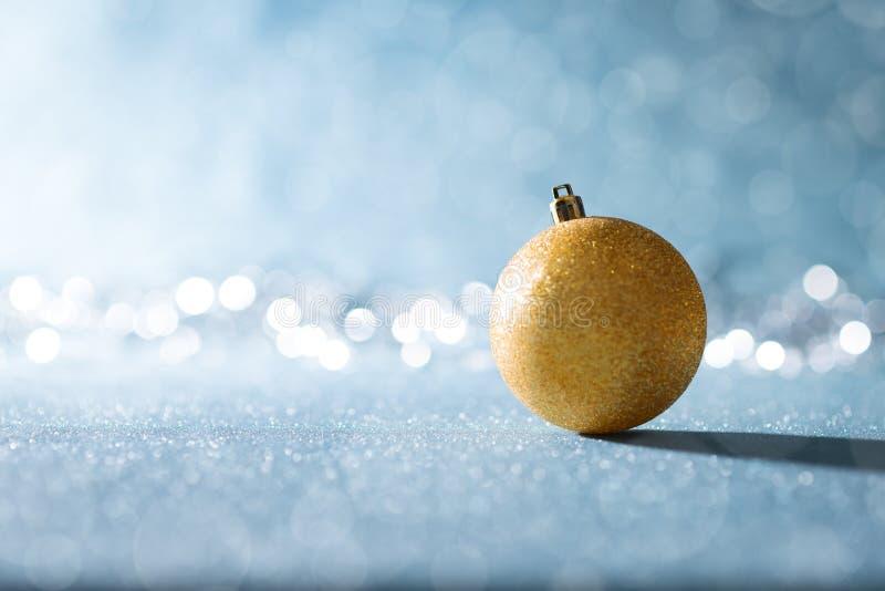 Błyszczący Złocisty Bożenarodzeniowy Bauble w zimy kraina cudów Błękitny Bożenarodzeniowy tło z defocused bożonarodzeniowymi świa fotografia stock