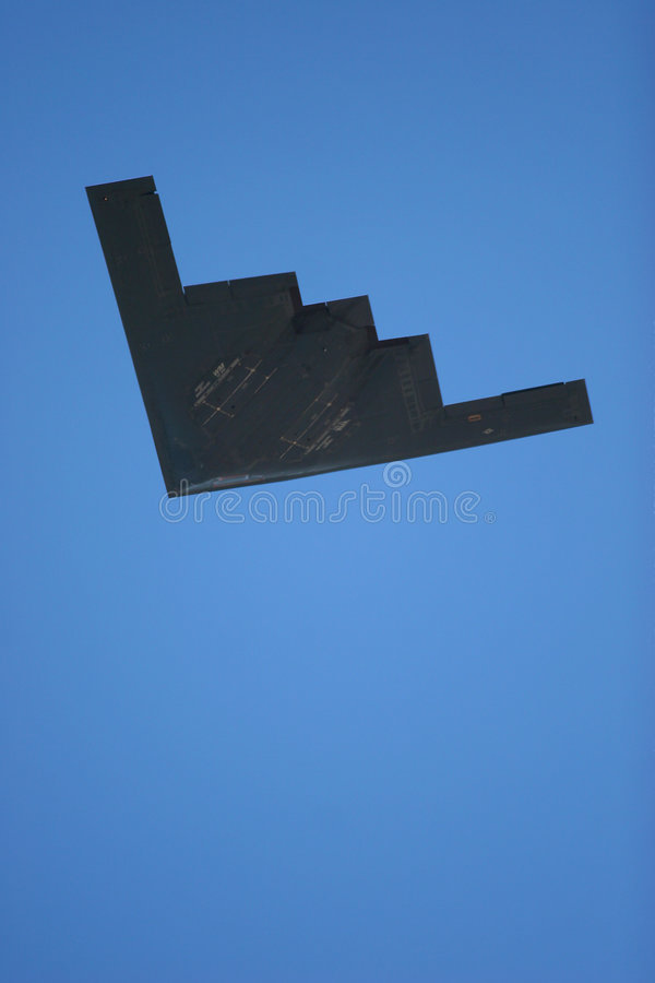 B-2 stealth bomber. During a low pass with blue sky, room for text stock image