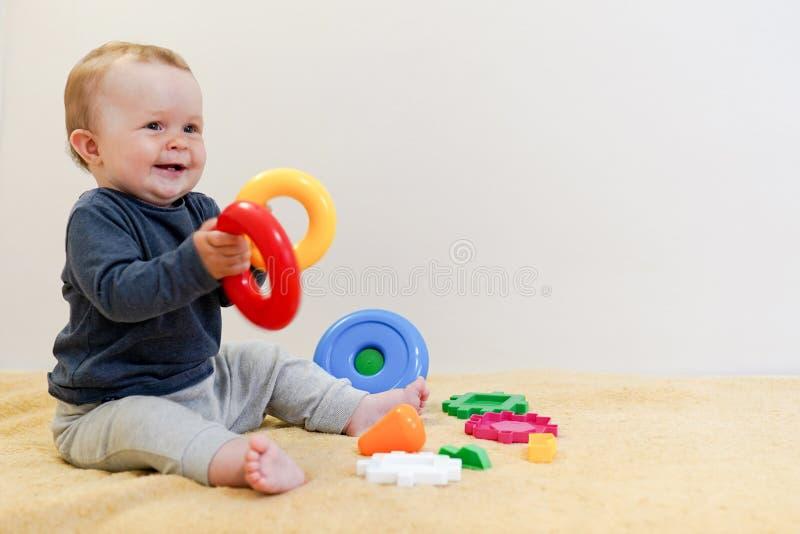 B?b? adorable jouant avec les jouets ?ducatifs Fond avec l'espace de copie Enfant en bonne sant? heureux ayant l'amusement ? la m images libres de droits