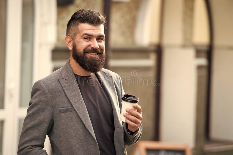 B?balo en camino Inconformista barbudo del hombre preferir caf? para llevarse Caf? de la bebida del hombre de negocios al aire li foto de archivo