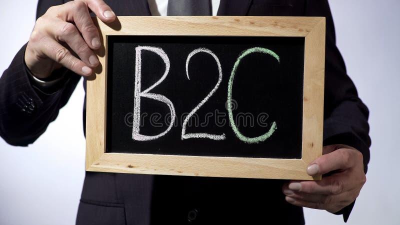 B2C, negocio-a-consumidor escrito en la pizarra, hombre de negocios que lleva a cabo la muestra fotos de archivo