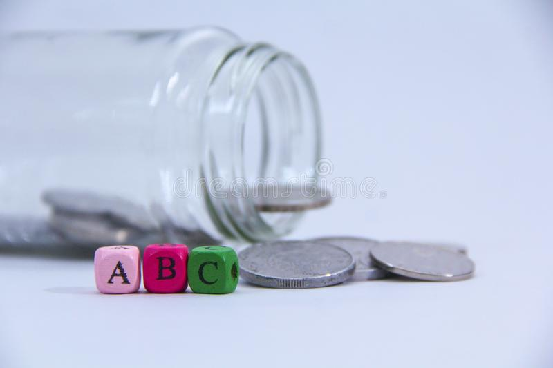 A,B and C in wooden block with coin at the back stock photo