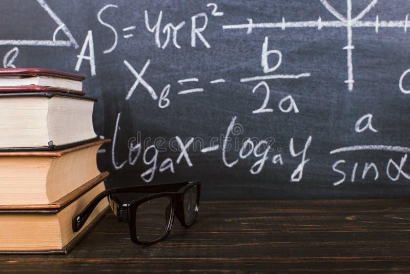 B?cker p? en tr?tabell, mot bakgrunden av ett kritabr?de med formler Teacher' s-dagbegrepp och baksida till skola arkivfoto