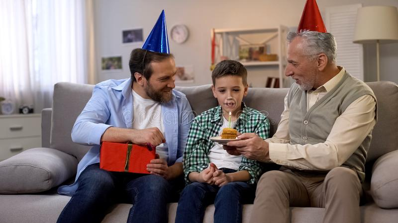B-day boy making wish blowing candle on cake, father and grandfather celebrating royalty free stock photo