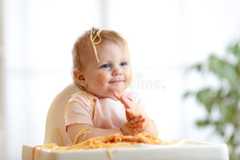 B?b? dr?le mangeant la nouille L'enfant encrassé mange des spaghetti avec handssitting sur la table à la maison image stock