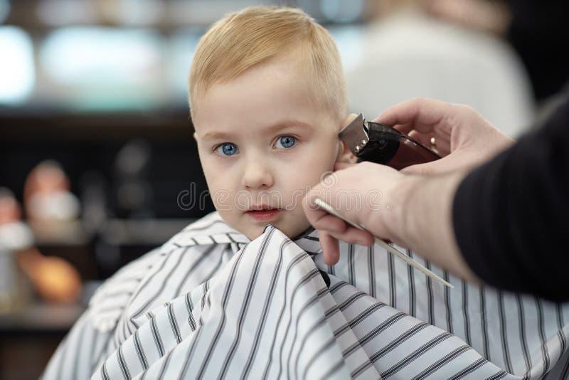 B?b? gar?on blond mignon effray? s?rieux et peu avec des yeux bleus dans un salon de coiffure ayant la t?te de lavage par le coif image libre de droits