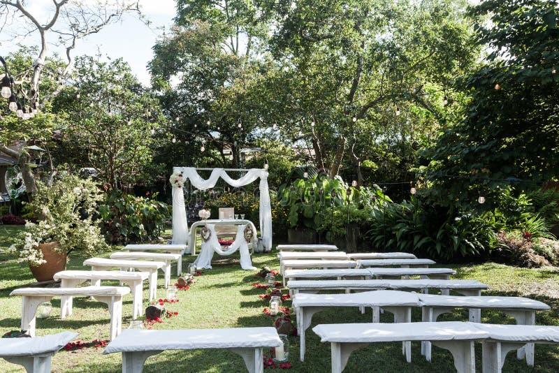 B?gen f?r br?llopceremoni, altare dekorerade med blommor p? gr?smattan royaltyfria foton
