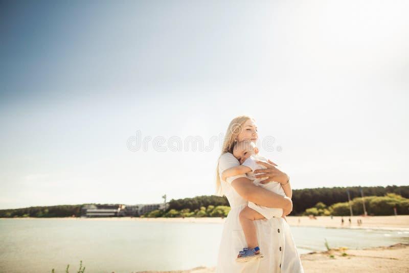 B?b? heureux de huges de m?re La m?re tient l'enfant dans des ses bras, b?b? ?treignant la maman photos stock