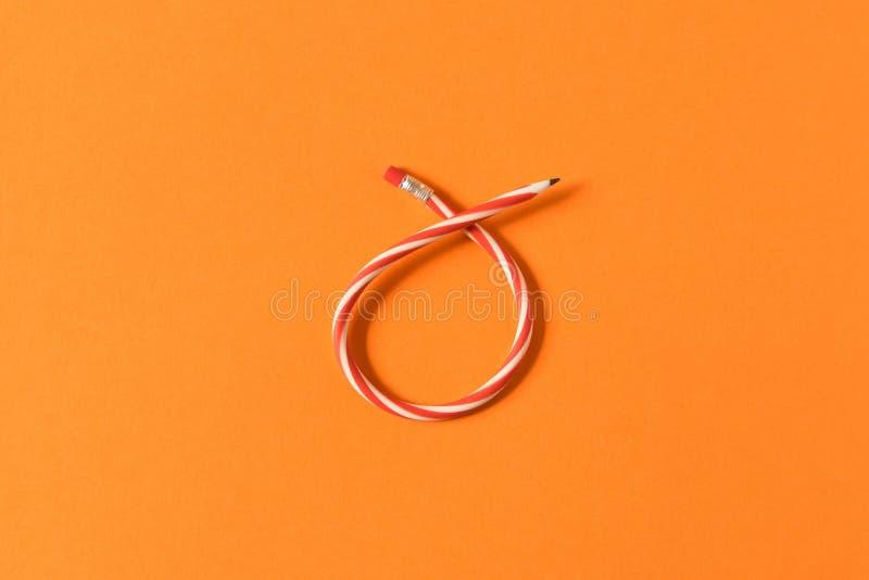 b?jlig blyertspenna Isolerat p? orange bakgrund B?jande blyertspenna arkivfoto