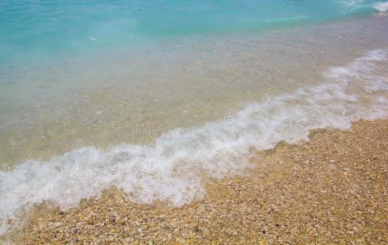 B??kitne wody z morze pian? Ma?e fale przychodz? brzeg Turkusowa lazur woda z białymi otoczakami na plaży Denna linia fotografia royalty free