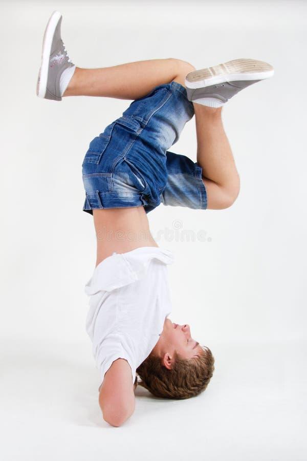 B-menino adolescente que está em sua cabeça no gelo imagens de stock royalty free