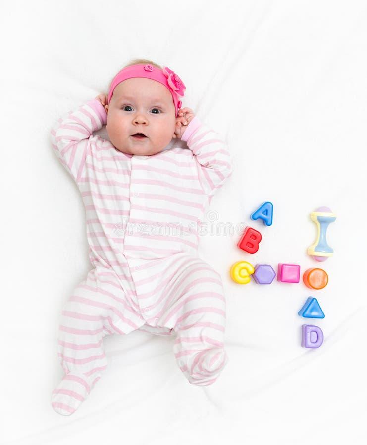 B?b? mignon jouant avec le jouet color? Enfant nouveau-né, peu de fille regardant la caméra et le mensonge B?b? apprenant le grip image stock