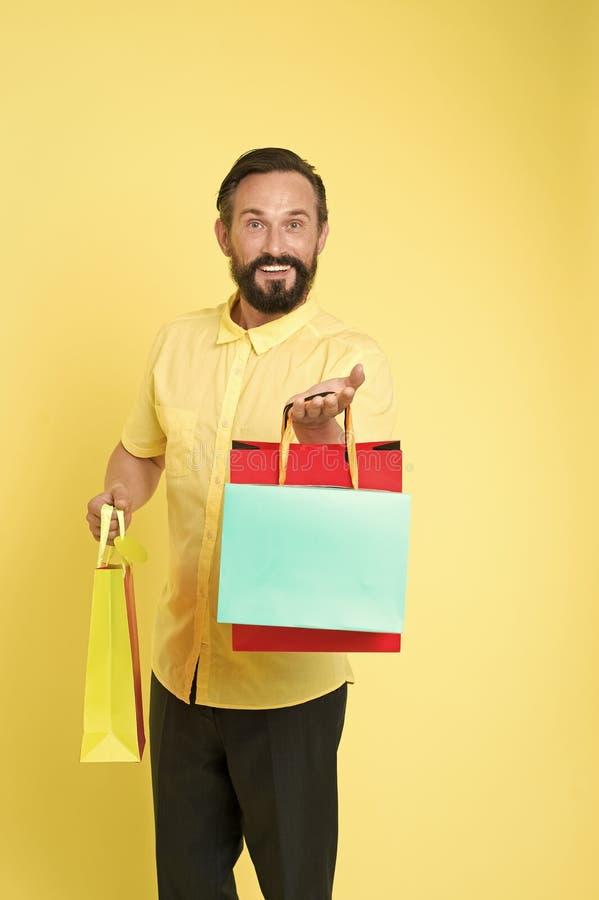B?nus da oferta para a boa ideia do cliente A cara alegre farpada madura do homem guarda sacos de compras O homem obteve presente imagem de stock