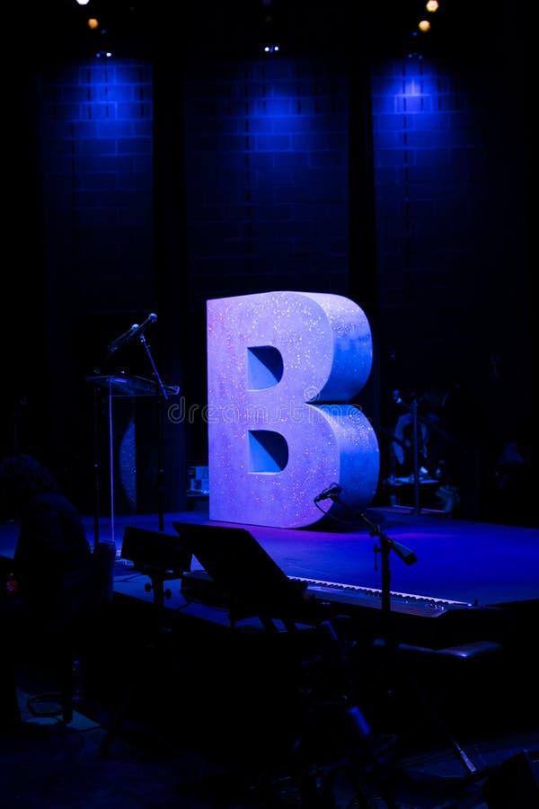 B pour Brooklyn sur une étape vide trempée dans la lumière bleue images libres de droits