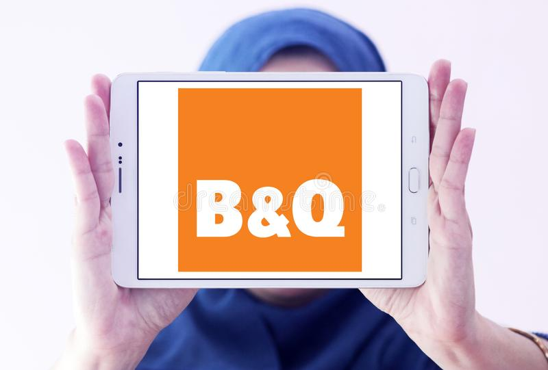 B&Q retailer logo. Logo of logo of B&Q retailer on samsung tablet holded by arab muslim woman. B&Q plc is a British multinational DIY and home improvement royalty free stock image